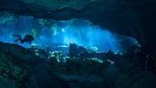 Diver exploring an underwater cave network