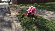 Lilies mark the spot where the body of Nisa Mickens was found