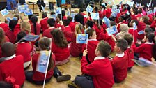 Cardwell Primary pupils wave flags at their Ten Pieces Assembly