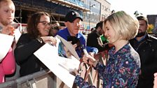 Jodie Whittaker signing autographs on the red carpet.