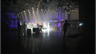 A large studio with a rock band playing. A variety of cameras and equipment are in the foreground.