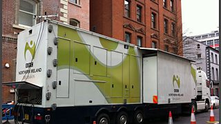 A large outside broadcast truck parked in a street.