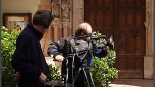 A camera man and sound man recording a broadcast in a church.