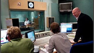 Three technical staff at audio controls look on into the studio through its glass window.