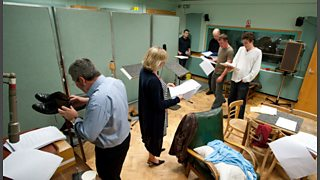 A variety of sound effects of feet walking are made during a drama recording in the radio studio