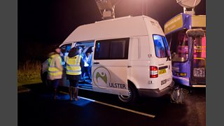 A Volkswagen Transporter van with a large satellite on top. BBC crew are working around it.