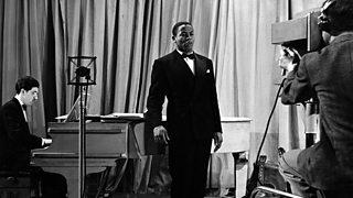A black man, Edric Connor, sings beside a piano. A cameraman records him.