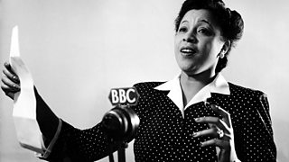 A black woman holding a script with a BBC microphone in the foreground.