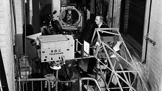 A BBC camera pointing down a complicated series of lenses and mirrors.