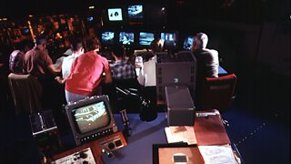 A TV production gallery - a mostly male crew watch a large bank of black and white TV screens.