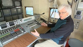 Brian Summers sits at the control desk with a large bank of TV screens and a communications panel with a microphone.