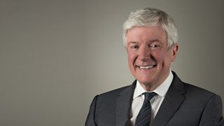 A smiling older man with white hair wearing a grey suit