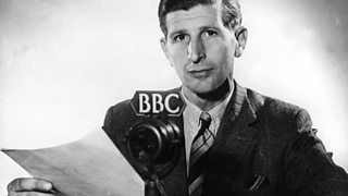 Newsreader and announcer, Alvar Lidell sitting behind a BBC microphone in 1946.