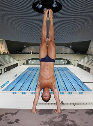 Olympic diver, Tom Daley performs a handstand before diving