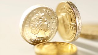 Two pound coins balancing on their side and two pound coins laid flat