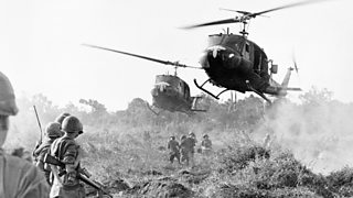 Rescue helicopters landing in a field in Vietnam as soldiers watch on