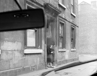 A car driving through the Gorbals area of Glasgow in 1963