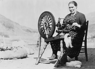 A middle-aged woman seated outside operating a spinning wheel