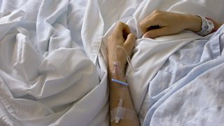 The arm of a hospital patient, with a drip attached