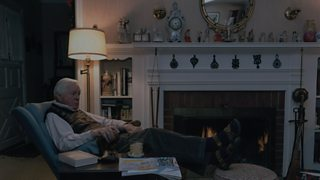 An old man, at home, sitting in an armchair by the fire