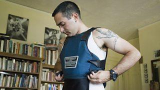 A man puts on a bulletproof vest