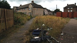 A boarded up housing estate with piles of dumped rubbish