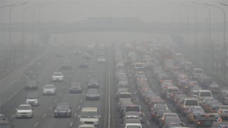 A five lane motorway full of cars and thick pollution