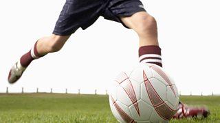 A teenage boy kicking a football