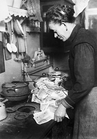 A German woman using money as fuel and putting it into her stove