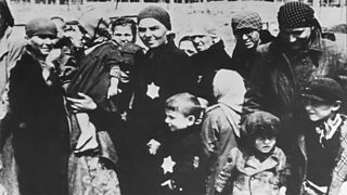 A group of Jewish men, women and children display the Star of David emblem on their clothing