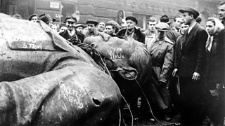 Crowd inspects fallen statue of Stalin.