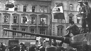 Freedom fighters sit on top of a tank with the revolutionary flag in Budapest