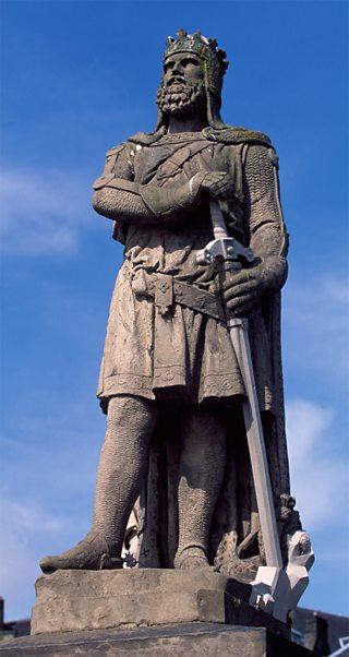Ìomhaigh de Raibeart Brus le chlaidheamh aig Caisteal Shruighlea