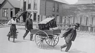 Police officer escorts Black American family moving house after the 1919 Chicago riots