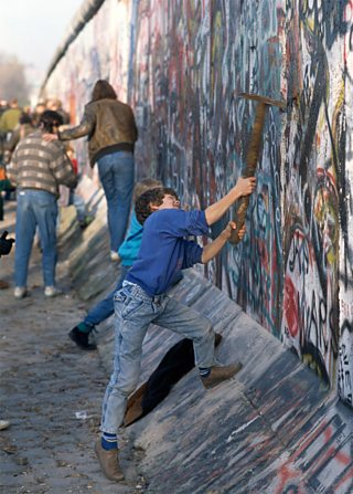 Youth swings pickaxe at Berlin Wall