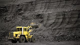 Big yellow mining truck in front of wall of coal at open pit mine.