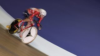 Cyclist racing around velodrome.