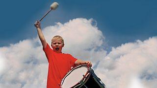 Boy holding mallet above drum.