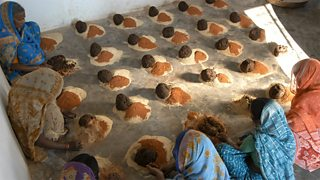 Women mixing ingredients to make cow dung soap in India.