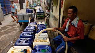 A street vendor fills his containers with clean water at a pump station in Jakarta