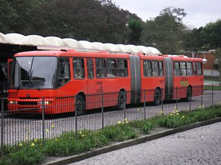 A bus station with a bendy bus waiting outside