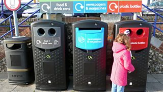 A small girl puts a bottle into a black plastic recycling bin