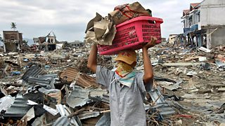 A man carries a basket of posessions through the mess left by the tsunami in Banda Aceh, Indonesia