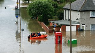 People in an emergency boat in a flood in Rotherham, UK