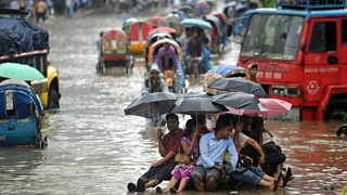 People attempt to stay dry over flood waters in the Bangladeshi capital of Dhaka
