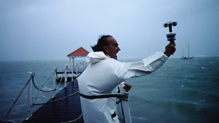 Man uses anemometer to measure the strength of the wind at sea