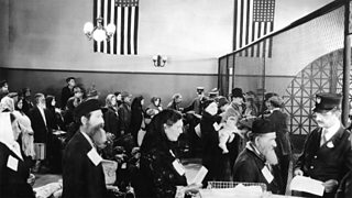Jewish people queuing at an office on Ellis Island.