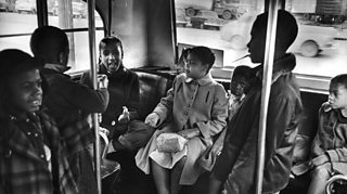 Photo of Linda Brown sitting at the back of a bus on her way to Monroe Elementary School