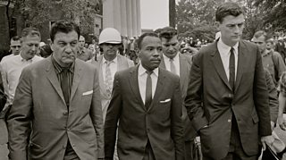 Photo of James Meredith walking to class accompanied by U.S. marshals.