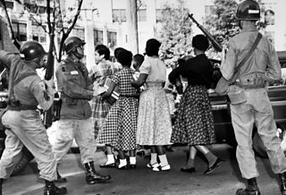 Photo of paratroopers watching black students enter Central High School, during the integration crisis that focussed on Little Rock in 1957